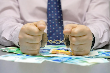 Businessman in office in handcuffs holding a bribe of Israeli money. Close-up hands in handcuffs. Arrested terrorist. Financial crime, dirty money and corruption concept. Focus on the handcuffs. Stock Photo
