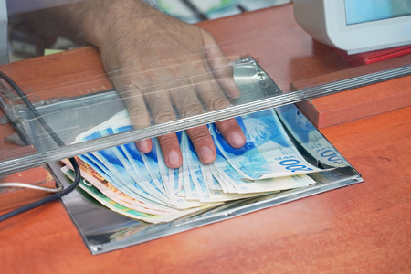 Cash money israeli shekel, at bank office or currency exchanger. Male hand with shekel money in cash department window. Currency exchange concept. Clerk giving cash money to customer at bank office.
