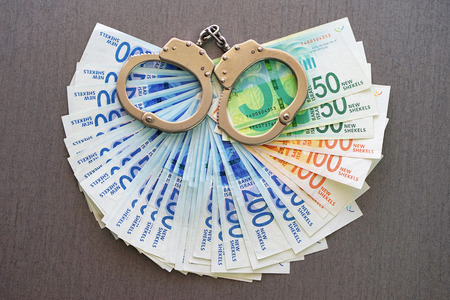 Handcuffs on the background of Israeli money. The new Israeli money bills (banknotes) of 50, 100 and 200 shekel. Police handcuffs. Financial crime, dirty money and corruption concept.