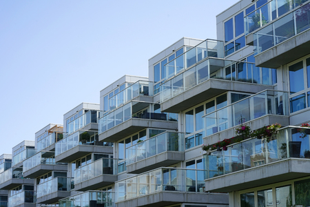 Closeup of an apartment building with balconies from the village. Background of windows and balconies of a multi-storey glass building. Stok Fotoğraf