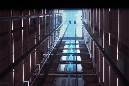 Aufzugskorridor im Gebäude durch blaue Beleuchtung beleuchtet. Der futuristische Aufzugsschacht befindet sich in einem hohen Turm. Aufzugsschacht in einem Wohngebäude. Abstrakter Hintergrund. Untersicht.