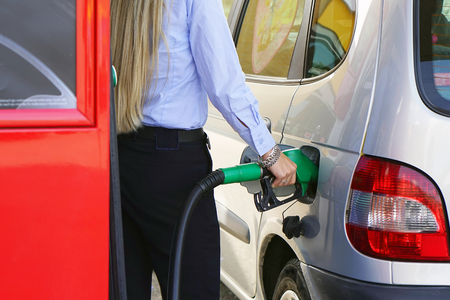 Woman fills petrol into her car at a gas station closeup. Woman hand holding a fuel pump at a station.