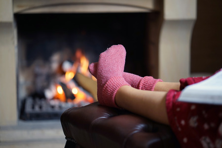 Woman feet with socks sitting near fireplace with a warmth background. Woman in warm socks resting near fireplace at home with book.