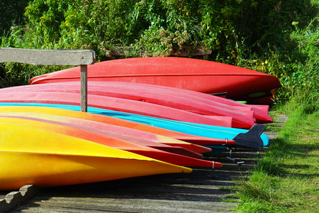 Multicolored inverted canoes on the shore. Multicolored inverted canoe boats