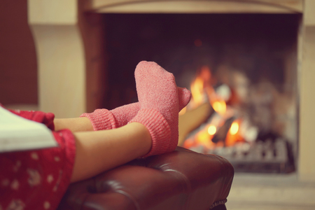 Woman feet with socks sitting near fireplace with a warmth background. Woman in warm socks resting near fireplace at home with book. Toning. Stock fotó