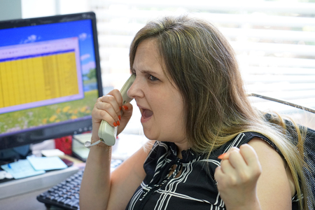 Close-up of an office worker swears with the client by phone. A woman is shouting into the phone's phone. Funny facial expressions, emotions, reaction of perception, stress, gilding, nerves. Stok Fotoğraf