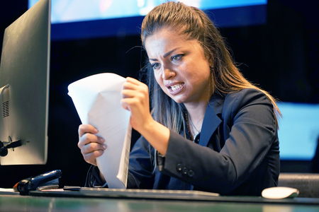 Office worker woman reading negative news in letter. Shocked beauty girl business manager received layoff message letter from company feeling surprised. Stockfoto