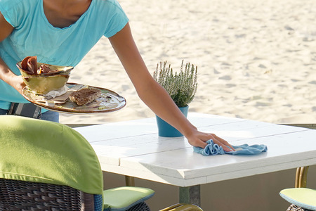 The waitress wipes the table in a cafe on the beach. A waitress is holding a tray with dirty dishes and leftover food. Waitress cleaning the table in a restaurant. The concept of service. Archivio Fotografico