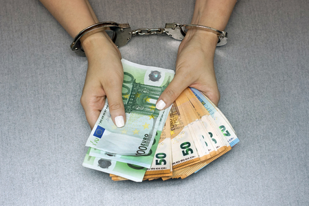Businesswoman in office in handcuffs holding a bribe of euro banknote. Close-up woman hands in handcuffs. Arrested terrorist. Financial crime, dirty money and corruption concept.