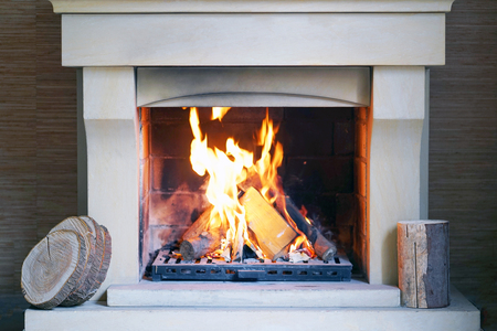 A warm fire in the stone fireplace on a cold night. Warm cozy fireplace with real wood burning in it. Cozy winter concept. Christmas and travel. Christmas backgrounds. Magic burning fireplace.