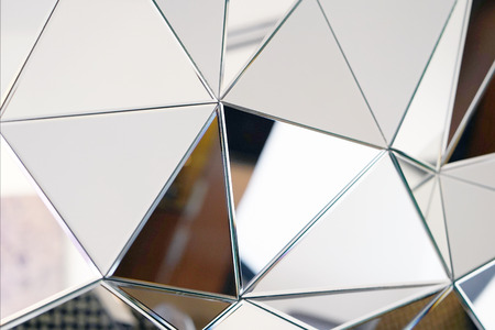 Mirror with crystals in wall, decoration and reflection. Abstract glass background. Polygonal surface. Close-up. Texture. Фото со стока