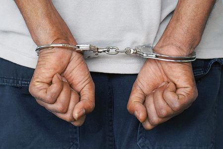 Close-up. Arrested man handcuffed hands at the back isolated on gray background. Prisoner or arrested terrorist, close-up of hands in handcuffs. Stock Photo