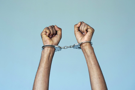 Close-up. Arrested african man handcuffed hands. Prisoner or arrested terrorist, close-up of hands in handcuffs. Isolated on gray background Stock Photo