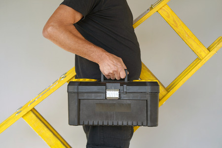 Electrician holds tool box and yellow wooden ladder. The builder carries a wooden ladder and toolbox on a gray background. Breeder with tool box and yellow wooden ladder. Standard-Bild