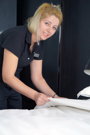 Maid making bed in hotel room. Housekeeper Making Bed Stock Photo