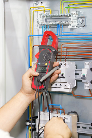 Electrician measures voltage with multimeter in electrical cabinet.