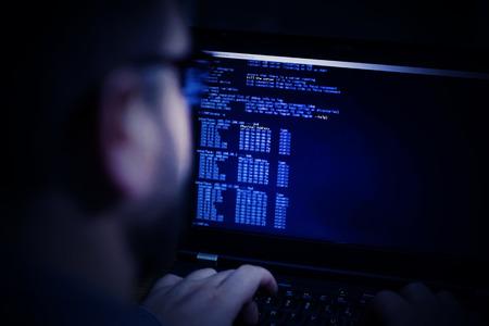 Hacker in glasses breaking code. Criminal hacker penetrating network system from his dark hacker room. Computer program writer at work. Rear view. Toning