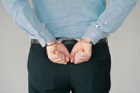 Close-up. Arrested man handcuffed hands at the back. Isolated on gray background. Businessman in office in handcuffs holding a bribe. Arrested man in handcuffs. Criminal hands locked in handcuffs. Stock Photo