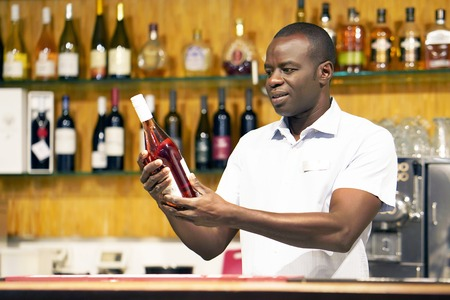 African bartender is holding a bottle of red wine. The barman examines a bottle of red wine.The bartender pours red wine to the client in the hotel bar. The concept of service. Concentrate on the bartender.