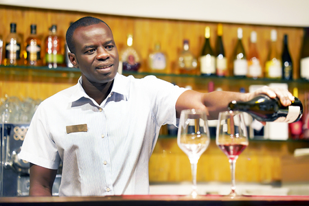 African barman men standing, pours red wine into a glass from a bottle. Shelves with bottles of alcohol in the background. Focus on the bartender. Stock Photo