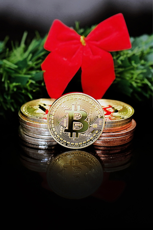 Close-up of decorating the Christmas tree of virtual currency Bitcoin on a black background. Christmas card. Physical bitcoin. The concept of cryptocurrency trading.