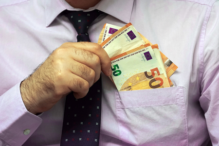 A businessman gives Euro a bribe to an employee in the office. Concept - corruption. Giving a bribe. Money in hand. The concept of corruption and bribery