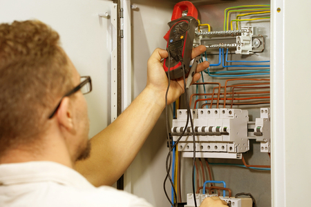 Electrician male measures voltage with multimeter in electrical cabinet. An electrician is checking the voltage in an electric box. Toning