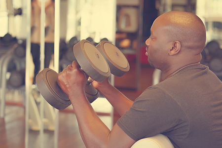 Hands of african man with dumbbells in the gym. Muscular man lifting a dumbbells on bench at gym, side view. Toning