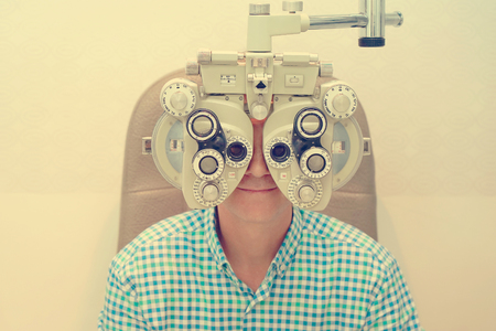 Male ophthalmologist examining patient man with optometrist trial frame. Man patient to check vision in ophthalmological clinic. Toning