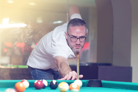 Male plays a billiard at the club. Caucasian mcaucasianan playing spending time on recreation. Play and fun concept. Toning