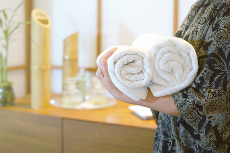 Chambermaid holding clean towels in spa. Clean white towel in a Spa centre. Staff cleaning lady holding towels at spa. Toning