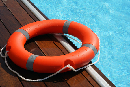 The red life ring lies on the wooden floor of the swimming pool. Life cycle, floating above the sunny blue water. Ring of life in the pool
