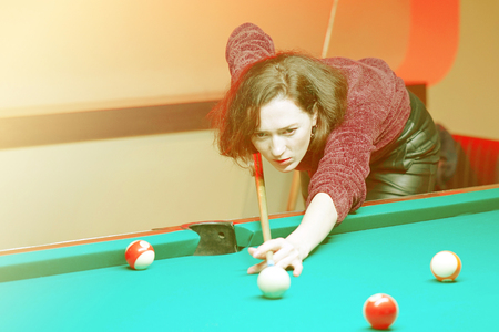 Young brunette girl playing snooker. Young happy woman having fun with billiard. Smiling fashionable woman playing spending time on recreation. Play and fun concept. Toning