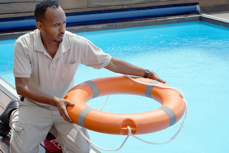 Hands of the rescuer with lifebuoy in pool. Hotel worker throws a lifeline to a drowning pool. Salvation of a sinking person. Life ring in swimming pool. Red lifebuoy pool ring. Standard-Bild