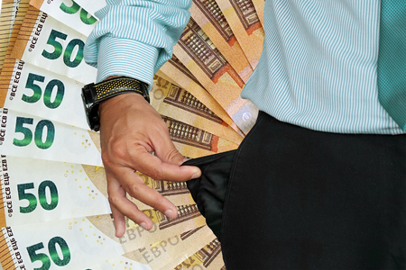 Close-up of hand of senior businessman in suit turning pocket of his trousers inside out and showing it empty. Crisis, unemployment, bankruptcy concept. Fan of 50 euro in the background. Banco de Imagens