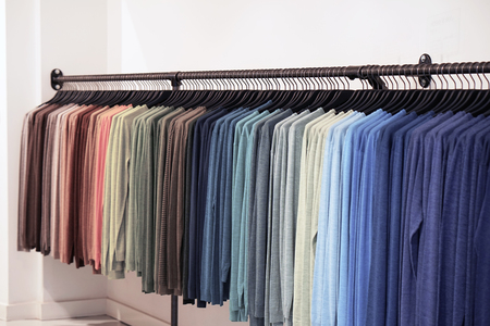 clothes hanger with t shirt. Fashionable clothing on hangers in shop. sport of T Shirts are hanging on Clothes Hanger , Colorful T Shirt Banco de Imagens