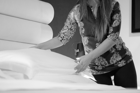 Maid making bed in hotel room. Housekeeper Making Bed. Black and white photography. Stock Photo
