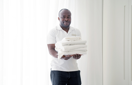 Portrait of african man a smiling hotel maid holding fresh clean folded towels for the room. Chambermaid man holding clean towels in hotel room Banco de Imagens
