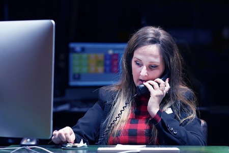 Close-up of an office worker. Woman secretary answering phone calls and talking with customers, she is sitting at her desk working. Night time. Toning.