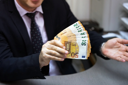 Bribe to an office worker, businessman. The concept is corruption. To give, take a bribe. Money, a pack of euros in a shirt pocket. The concept of corruption and bribery.
