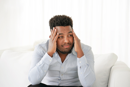 African Man suffering from headache migraine pain at home on sofa. Health problem, stress and depression. Male holds head with hand. Concept of health.