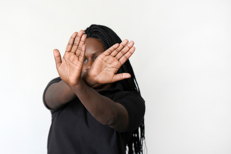 African woman hide her face at hand isolated on white background. Woman holding her hand stretched out toward the camera, covering her face, avoiding to be seen or stopping a problems