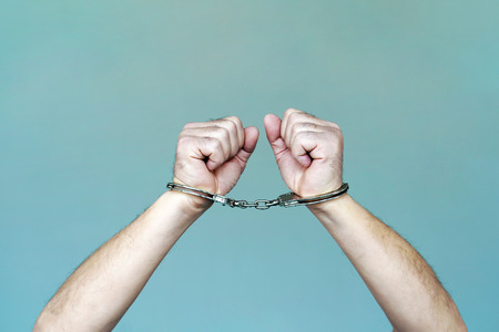 Close-up. Arrested man handcuffed hands. Prisoner or arrested terrorist, close-up of hands in handcuffs Фото со стока