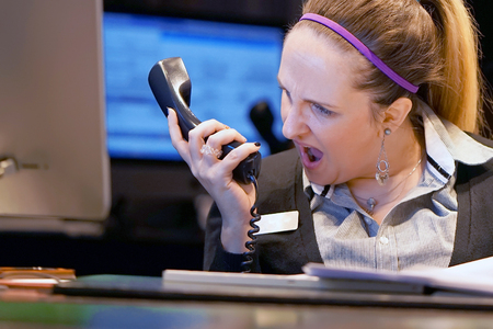 Woman-reception swears with the client of the hotel by phone. A woman is shouting into the phones phone. Funny facial expressions, emotions, reaction of perception, stress, gilding, nerves. Stock Photo