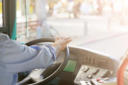 현대 버스에서 운전하는 운전자의 손입니다. 개념 - 버스 운전사와 운전하는 승객 버스의 클로즈업. 토닝