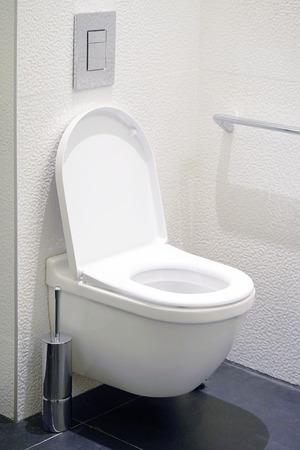 Close-up van toiletpot en rol op toiletpapierhouder. Wc-papierrol in toilet. Openbaar toilet in de luchthaven of restaurant, café.