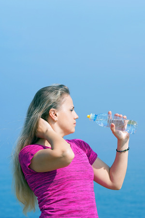Side view of beautiful girl in sport clothes drinking water after workout on the beach. Young woman drinking from a Water Bottle on the background of the sea. Concept of health. Stockfoto