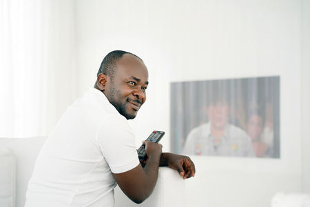 Handsome young African man holding a remote control and laughing while sitting on the sofa at home. man enjoying movie or show in entertainment concept