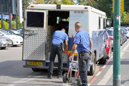 Deux hommes des gardes du Camion de la Compagnie Brink's ont mis les sacs d'argent dans la voiture. gardes transportant de l'argent. Voitures blindées bancaires. des gardes armés transportant de l'argent. 11 novembre Tel-Aviv, Israël. Éditoriale