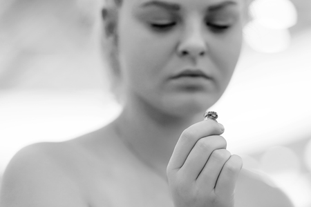 Black and white photography. Woman holding wedding engagement ring in hands, engaged girl doubts about marriage proposal, abandoned wife depressed after getting divorced, help to overcome breaking up